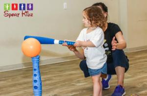 Sports kids. Toddler kitting a balloon ball with a baseball bat