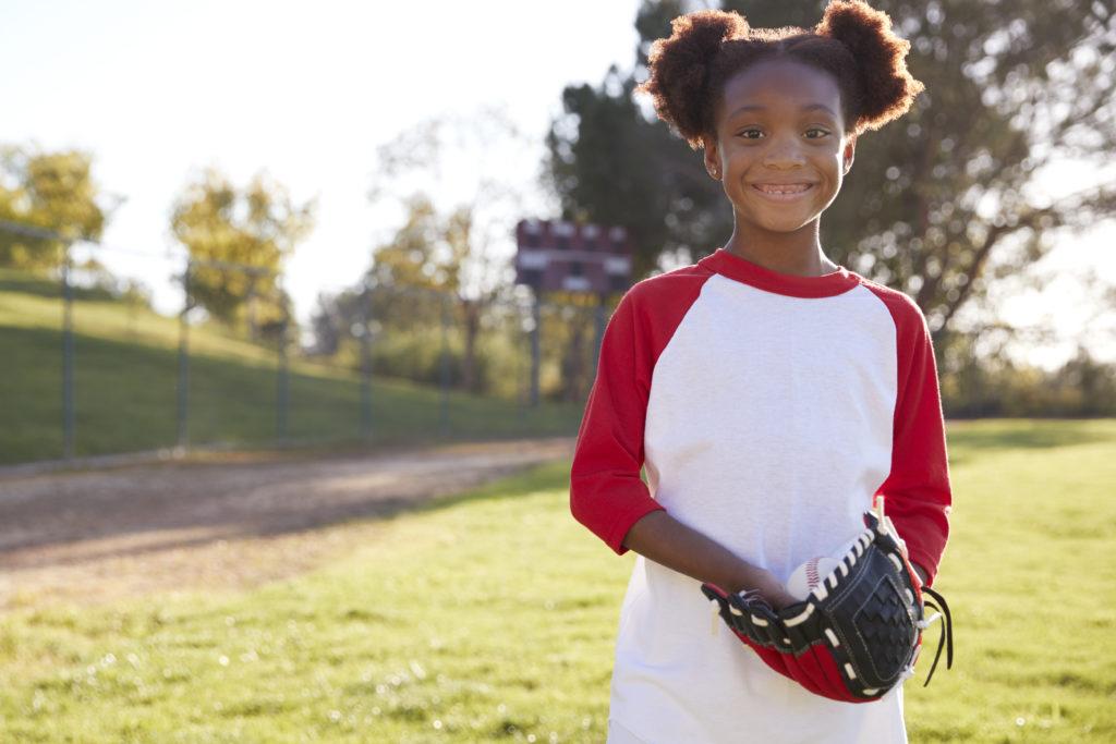 Young Black girl holding baseball mitt smiling to camera