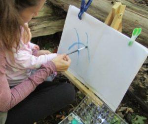 Little girl exploring art on a canvas